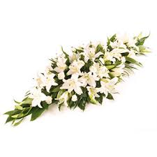 funeral spray white lilly flowers arranged in funeral casket spray delivered in