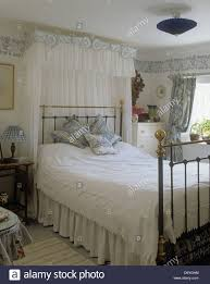 white voile drapes above bed with white linen in all white