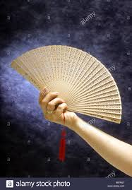 woman hand hold wood chinese fan with red tassel spread cool