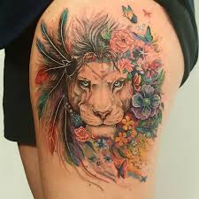 feminine lion with feathers colorful tattoo on thigh