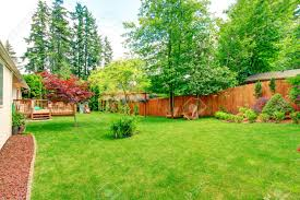 fenced backyard with green lawn flower beds and romantic sitting