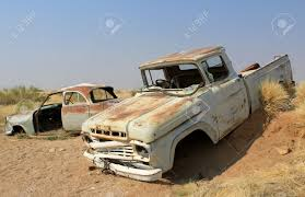 old and rusty car wreck at the last gaz station before the namib