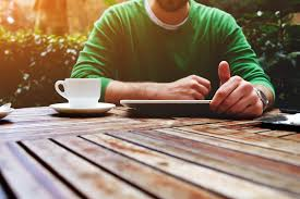 young man sitting at the table with cup of coffee digital tablet