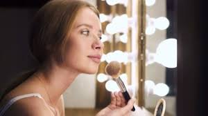 looking for makeup artist girl looking in mirror and applying cosmetic with lip pencil