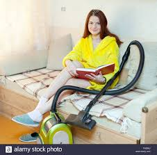 tired woman rests from household chores with book in home stock