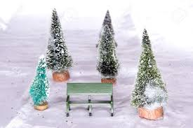miniature park bench with snow covered christmas trees on snow