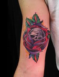 skull in purple rose tattoo on inner bicep