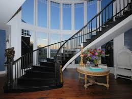 gothic curved black staircase is designed beside round table also