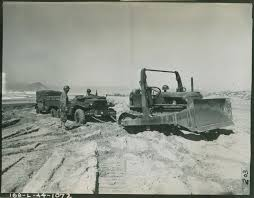 amphibious vehicle ww2 army bulldozer pulling jeeps and trailers through sand during