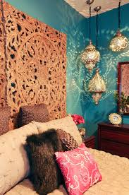 rich teal walls moroccan lanterns and a dramatic headboard made