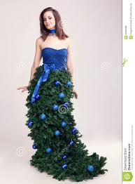 woman in christmas tree dress on grey background stock photo