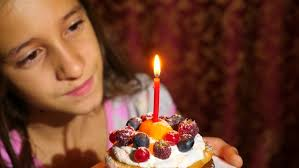 happy young blowing out candles on a birthday cake stock