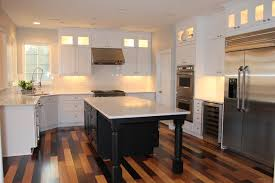 white kitchen with black island multi colored bamboo flooring