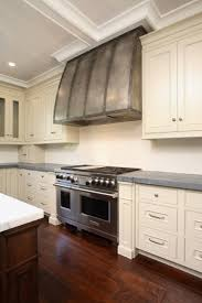 large kitchen with barrel range hood with forged iron straps