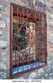 Square glass window with wrought iron decorative panel in front