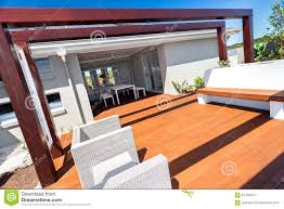 chairs in outdoor seating area under dark brown wooden pillars