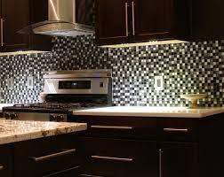 interior brown mosaic tile backsplash with glass flower vase on