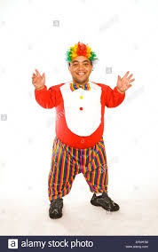 full length portrait of a happy midget clown against a white stock