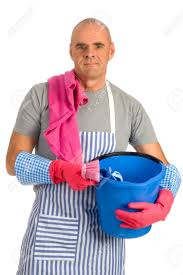 Cleaning The House by Houseman Is Cleaning The House With Apron And Tools Stock Photo