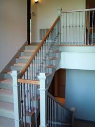 nice staircase with light wood and white railing and wrought iron