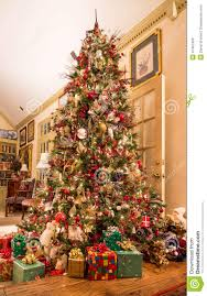 presents under decorated christmas tree in den stock photo image