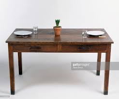 old wooden desk doubling as dining table set with plates cutlery