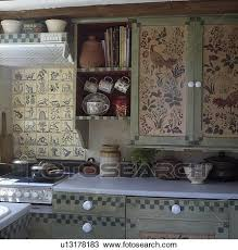 Cottage Kitchen Cupboards - stock photo of flowers and birds painted on to cupboards in