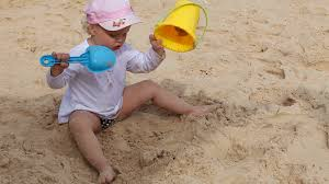 little playing bucket and shovel dig on sand beach sea stock
