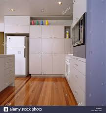 wooden flooring in modern white kitchen with large fridge freezer