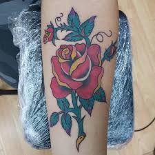 red rose and green leaves tattoo on forearm