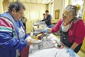 volunteers serve the needy during free thanksgiving dinner at