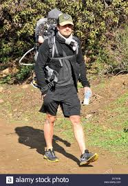 orlando bloom carries his flynn on his back while walking