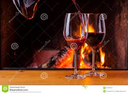 pouring red wine at cozy fireplace royalty free stock photography