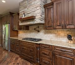 going have herringbone travertine backsplash with espresso stone hood vent with wood ledge travertine backsplash distressed stained cabinets bellahomesiowa