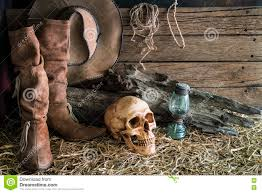 cowboy hat halloween human skull and cowboy boots in barn background stock photo