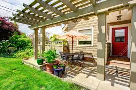 backyard porch with red door and attached pergola view of table