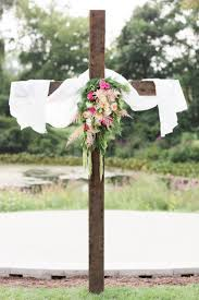 wooden cross with pink and green flowers wedding ceremony