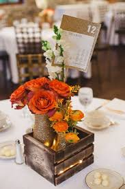 rustic center pieces picture of a crate with bold orange and blooms glittered vases