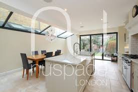 side return kitchen extension with sloping glass roof in fulham the island provides a social hub for the room as it enables food prep to be done simultaneously whilst chatting to others gathered around the island