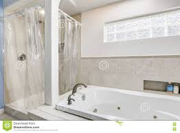 white clean bathroom with beige tile trim and small window stock