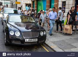 bentley london a passing pedestrian admires a bentley car parked on a single