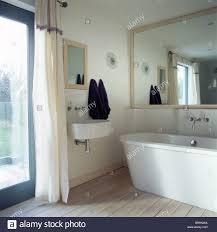 large mirror above modern bath in small modern bathroom with wall