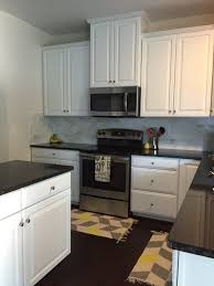 black and white kitchen with honed marble backsplash and uba tuba