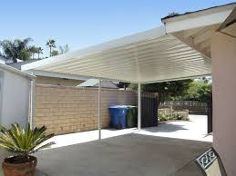 brick fence of modern carport has white pole it also has white