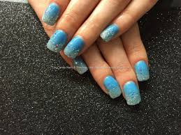 social build acrylic nails with blue gel polish and glitter dust