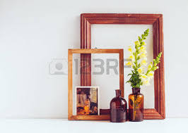 vintage blank wooden frame bottles and rose in a pot on a white