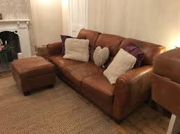 grand saddle leather sofas and foot stools with dark wood feet