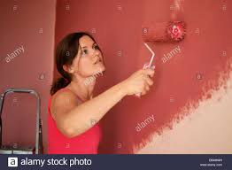 painting a wall beautiful young woman in causal clothes painting a wall with red