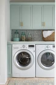 Laundry Room Pictures To Hang - gray green shaker cabinets adorned with brass pulls hang over a