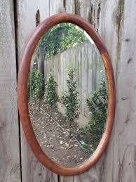 for sale is one large vintage wood oval beveled mirror this